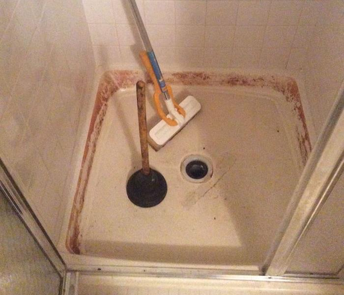 Shower pan with brown stains on the tile