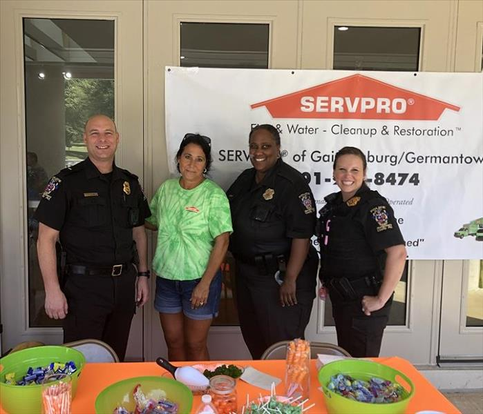 Policeman and policewomen and SERVPRO employee standing behind table with candy