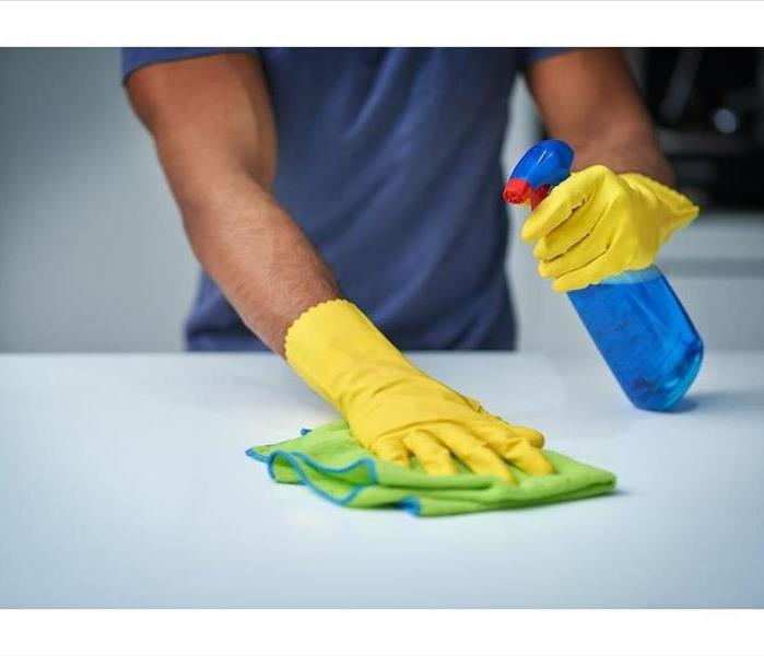 yellow gloved hand holding a blue bottle and a green rag wiping a counter