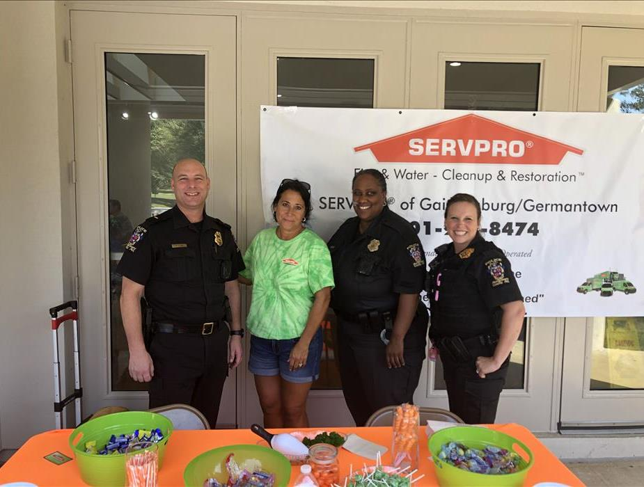 A female SERVPRO employee standing with 3 police officers.